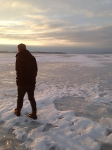 Walking on the frozen lake at sunset.
